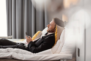 Side view of businessman listening to music while lying on bed at hotel roomの写真素材 [FYI02143701]