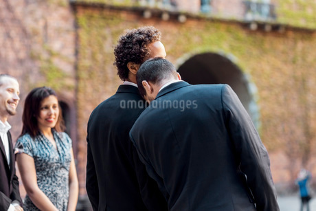 Rear view of gay man leaning on partner's shoulder during wedding ceremonyの写真素材 [FYI02143731]