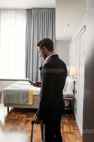 Side view of businessman using mobile phone standing with luggage in hotel roomの写真素材 [FYI02143736]