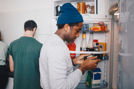 Side view of man looking at food package standing by refrigerator in kitchenの写真素材 [FYI02143748]