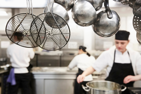 Kitchen utensils with chefs cooking in background at commercial kitchenの写真素材 [FYI02143779]