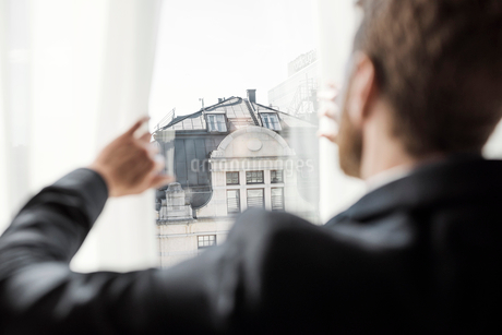 Rear view of businessman looking at building through hotel windowの写真素材 [FYI02143793]