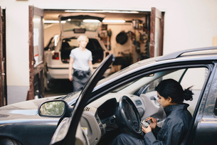 Side view of female mechanic using mobile phone while sitting in carの写真素材 [FYI02143800]