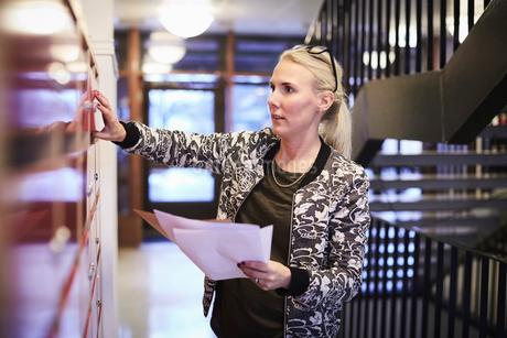 Mid adult teacher holding papers while opening locker in school corridorの写真素材 [FYI02143830]