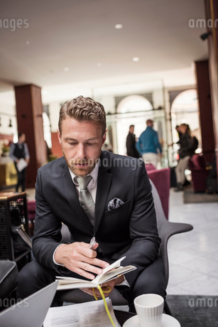 Businessman sitting in hotel reception reading documentの写真素材 [FYI02143861]