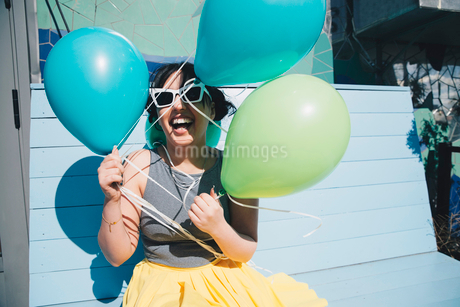 Happy young woman holding balloons while sitting on benchの写真素材 [FYI02143866]