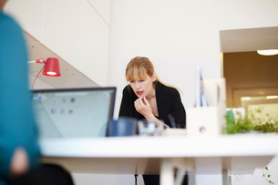 Mid adult businesswoman working at table in officeの写真素材 [FYI02143880]