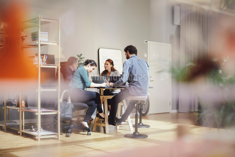 Business professionals are discussing while sitting with laptops at desk in creative officeの写真素材 [FYI02143893]