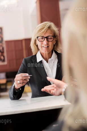 Happy mature businesswoman paying receptionist with credit card at hotel checkoutの写真素材 [FYI02143939]