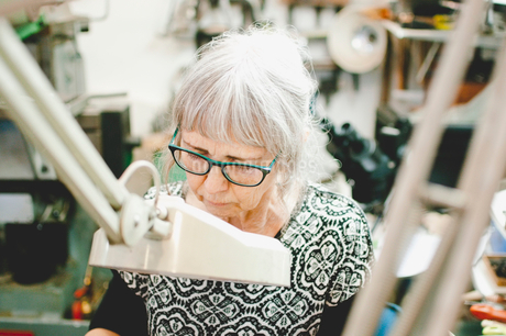Senior woman wearing glasses while working in jewelry workshopの写真素材 [FYI02143944]