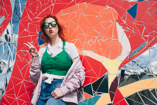 Portrait of redhead young woman wearing sunglasses while gesturing peace sign against mosaic wallの写真素材 [FYI02143965]