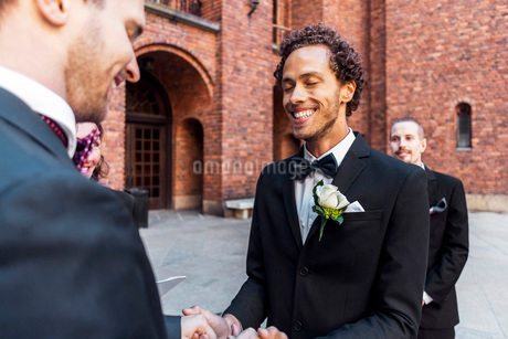 Man holding hands of gay partner with friend standing in backgroundの写真素材 [FYI02144000]