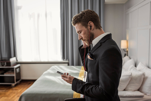 Side view of businessman listening to mobile phone in hotel roomの写真素材 [FYI02144001]