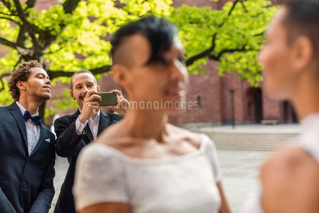 Male friend photographing lesbian couple during wedding ceremonyの写真素材 [FYI02144013]