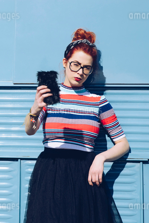 Redhead young woman taking selfie while standing against mini vanの写真素材 [FYI02144059]