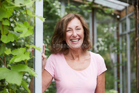 Portrait of happy senior gardener standing at entrance in yardの写真素材 [FYI02144071]