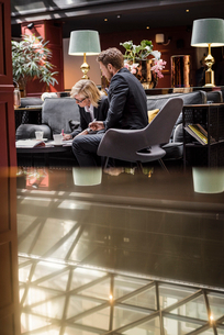 Businesswoman signing agreement by male partner sitting in hotel receptionの写真素材 [FYI02144080]