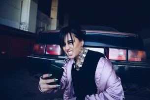 Portrait of young woman taking selfie by car in parking lotの写真素材 [FYI02144098]
