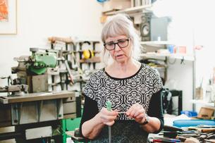 Senior woman holding work tool in jewelry workshopの写真素材 [FYI02144102]