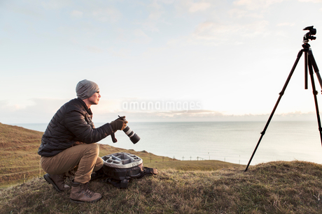 Side view of hiker looking away while holding SLR camera on hill by sea against skyの写真素材 [FYI02144109]