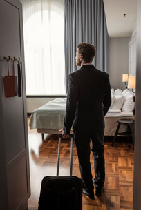Rear view of businessman with luggage standing in hotel roomの写真素材 [FYI02144131]