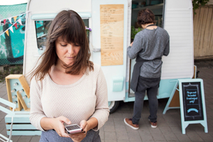 Female owner using smart phone outside food truck while colleague working in backgroundの写真素材 [FYI02144133]