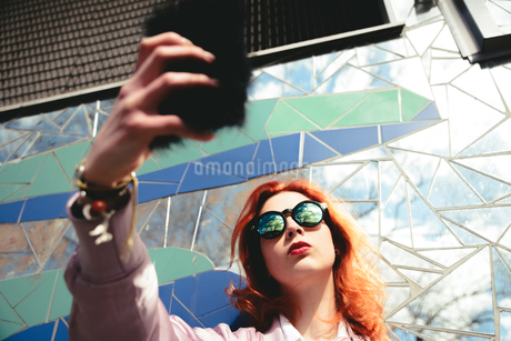 Low angle view of redhead young woman taking selfie with mobile phone against mosaic wallの写真素材 [FYI02144154]