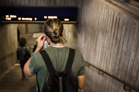 Rear view of man carrying backpack while walking down steps at subway stationの写真素材 [FYI02144205]