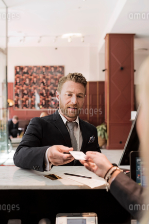 Businessman giving credit card to receptionist at hotel receptionの写真素材 [FYI02144263]