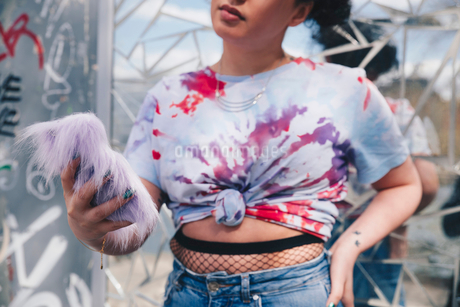 Midsection of young woman holding mobile phone against mosaic wallの写真素材 [FYI02144279]