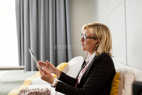 Side view of mature businesswoman using digital tablet sitting on bed at hotel roomの写真素材 [FYI02144284]