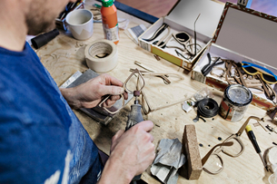 High angle view of owner making eyeglasses with work tool at workshopの写真素材 [FYI02144296]