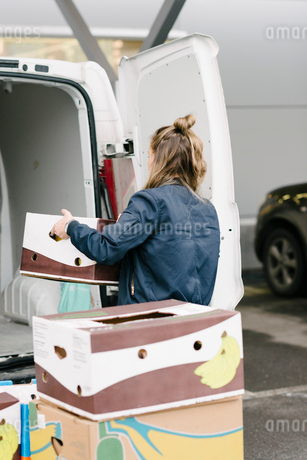 Rear view of delivery woman holding cardboard box by vanの写真素材 [FYI02144303]