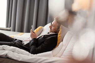 Side view of businessman listening music while lying on bed at hotel roomの写真素材 [FYI02144338]
