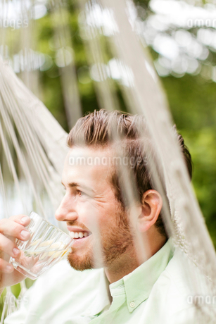 Smiling man drinking while resting in hammockの写真素材 [FYI02144345]