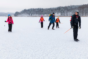 Family and friend ice-skating on frozen lakeの写真素材 [FYI02144354]