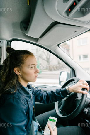 Side view of female worker driving with mobile phone in delivery vanの写真素材 [FYI02144360]