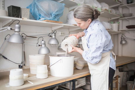 Senior female potter pouring clay from vase in bucket on workbench at workshopの写真素材 [FYI02144363]
