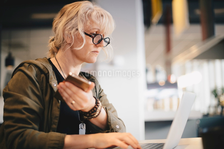 Businesswoman holding smart phone while using laptop at desk in officeの写真素材 [FYI02144368]