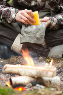 Low section of man rubbing beeswax on pant by campfireの写真素材 [FYI02144392]