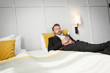 Businessman lying on bed while listening to music from mobile phone in hotel roomの写真素材 [FYI02144395]
