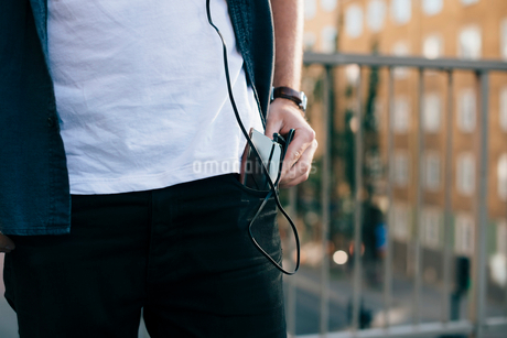 Midsection of man removing mobile phone from pocket in cityの写真素材 [FYI02144396]