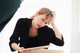 Confused businesswoman scratching head while using digital tablet in officeの写真素材 [FYI02144466]