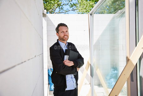 Businessman holding file with arms crossed while standing at construction siteの写真素材 [FYI02144480]