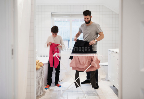 Son and father drying clothes on rack at homeの写真素材 [FYI02144487]