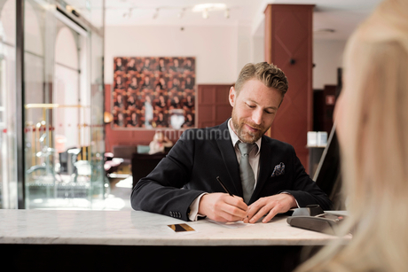 Mature businessman paying through credit card at hotel receptionの写真素材 [FYI02144494]