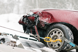 Damaged maroon car on tow truck during winterの写真素材 [FYI02144501]