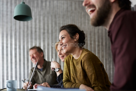 Cheerful creative business colleagues sitting at conference table while looking away in board roomの写真素材 [FYI02144502]