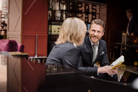 Happy businessman looking at female partner during meeting in hotel receptionの写真素材 [FYI02144535]