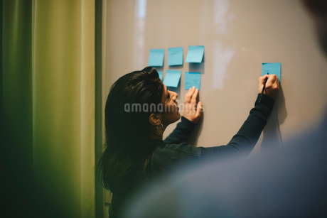 Rear view of businesswoman analyzing adhesive notes stuck on whiteboard in officeの写真素材 [FYI02144558]